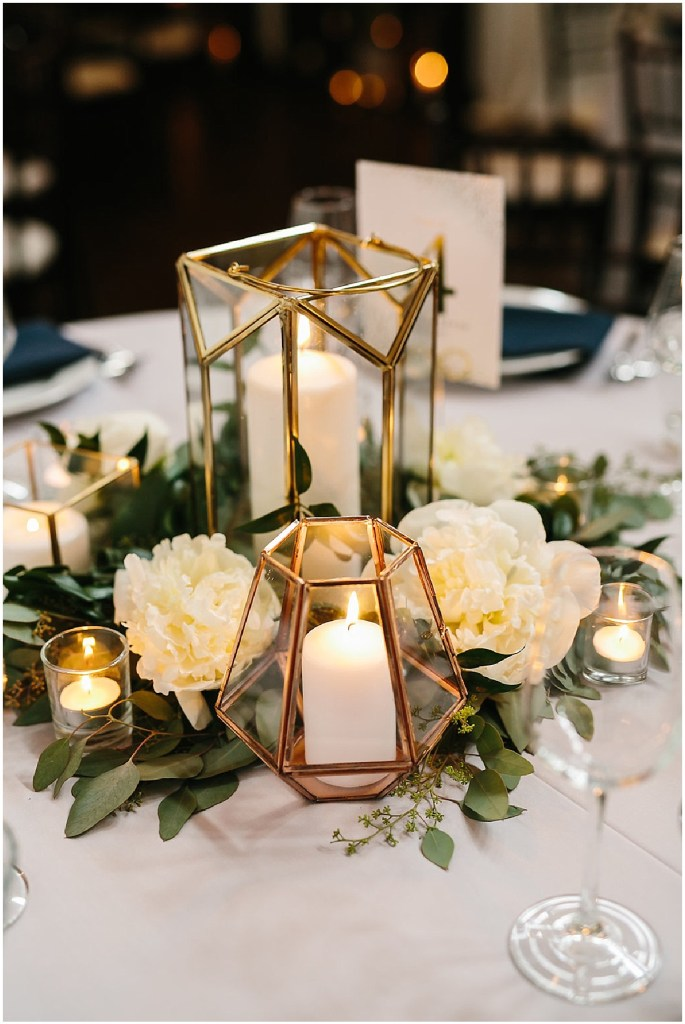 Wedding reception table centerpiece with geometric copper and glass candles holders, greenery, and ivory florals, same sex wedding, Sodo Park wedding, Seattle wedding coordinator, Perfectly Posh Events, Photo by Melissa Kilner Photography