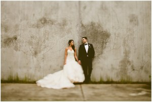 Bride wearing a mermaid cut gown poses with her groom in front of a cement wall, DeLille Cellars wedding, Woodinville winery wedding, Perfectly Posh Events wedding design, Photo by Andria Lindquist