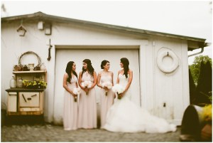 Bride in white mermaid gown poses in front of a white barn with her three bridesmaids wearing blush pink gowns, DeLille Cellars wedding, Woodinville winery wedding, Perfectly Posh Events wedding design, Photo by Andria Lindquist