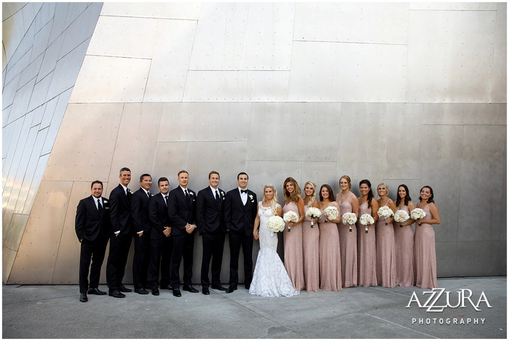 Bride and groom pose outside with their bridesmaids in blush colored gowns and groomsmen in black tuxedos in front of a large metal wall outside Seattle