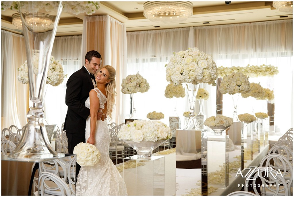 Bride and groom embrace while posing in their all-white wedding ceremony setup indoors with white chairs and a raised runway framed with large ivory floral bouquets sitting on lucite pillars, Four Seasons wedding, Seattle wedding, Perfectly Posh Events event coordination, Photo by Azzura Photography