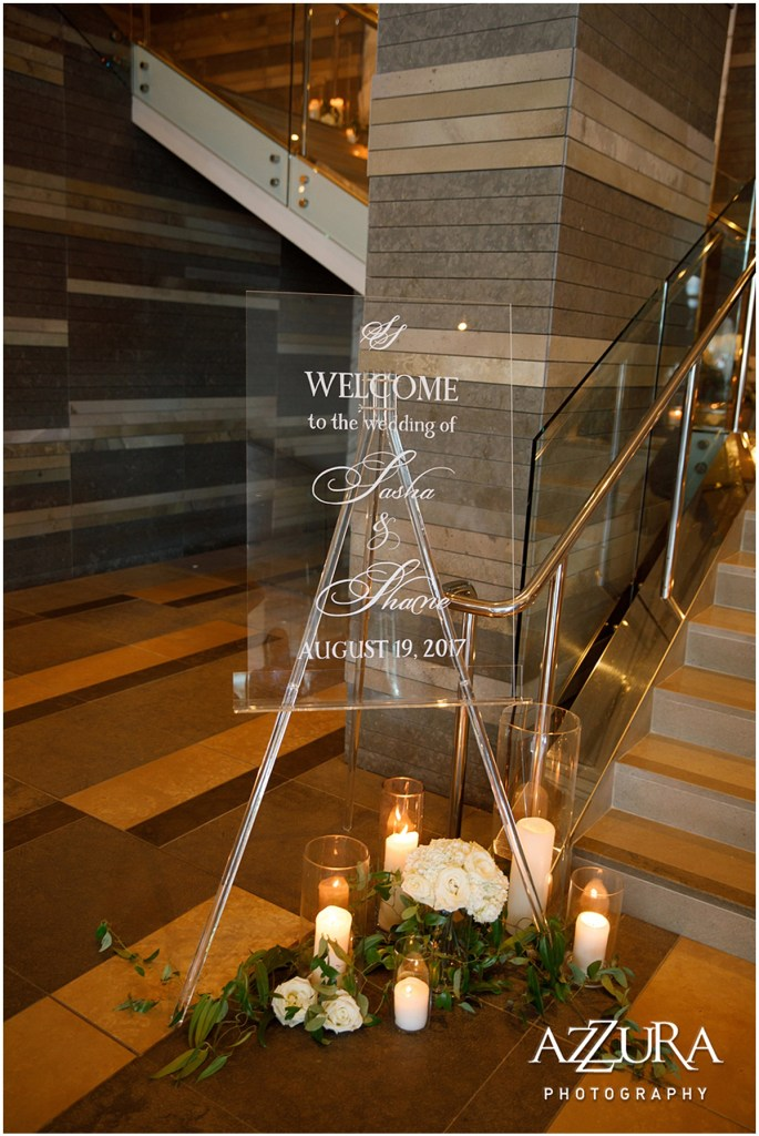 A custom designed wedding welcome design is etched onto a clear lucite frame surrounded with large pillar candles, ivory flowers, and greenery, Four Seasons wedding, Seattle wedding, Perfectly Posh Events event coordination, Photo by Azzura Photography