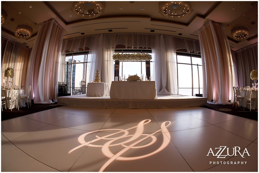 A white dance floor with a light display of the bride and grooms initials sits in front of in front of the couple table at a wedding reception, Four Seasons wedding, Seattle wedding, Perfectly Posh Events event coordination, Photo by Azzura Photography