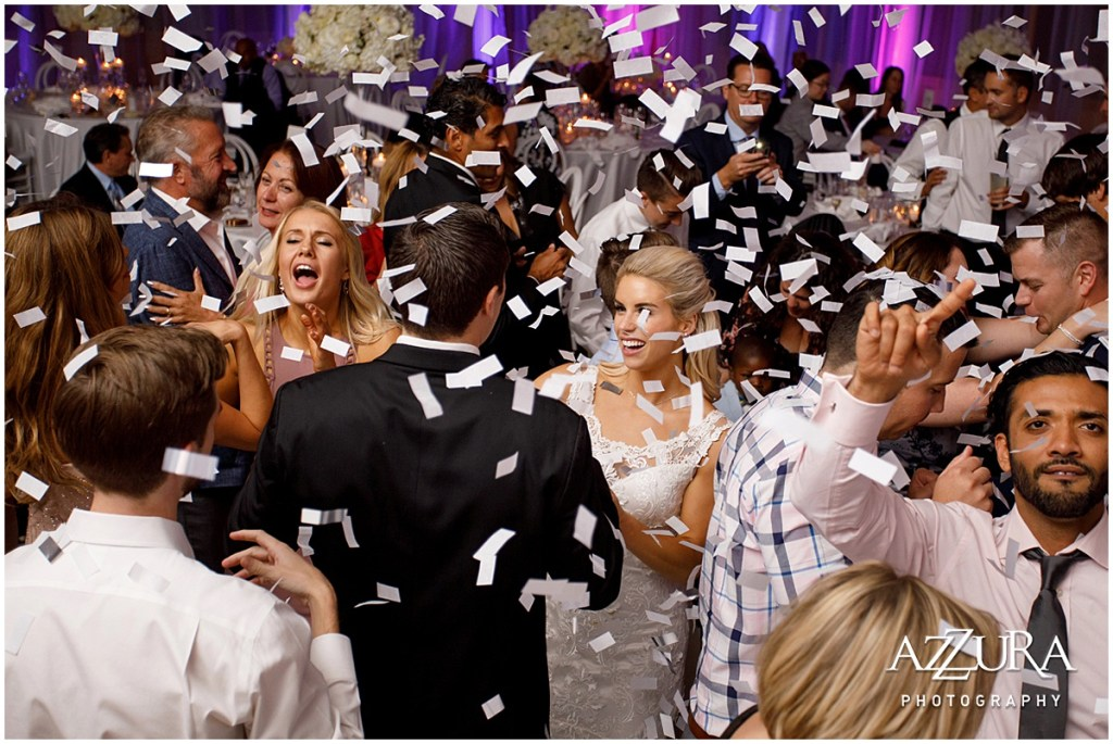 Bride and groom dance with their friends and family during their wedding reception while large white confetti flutters around them, Four Seasons wedding, Seattle wedding, Perfectly Posh Events event coordination, Photo by Azzura Photography