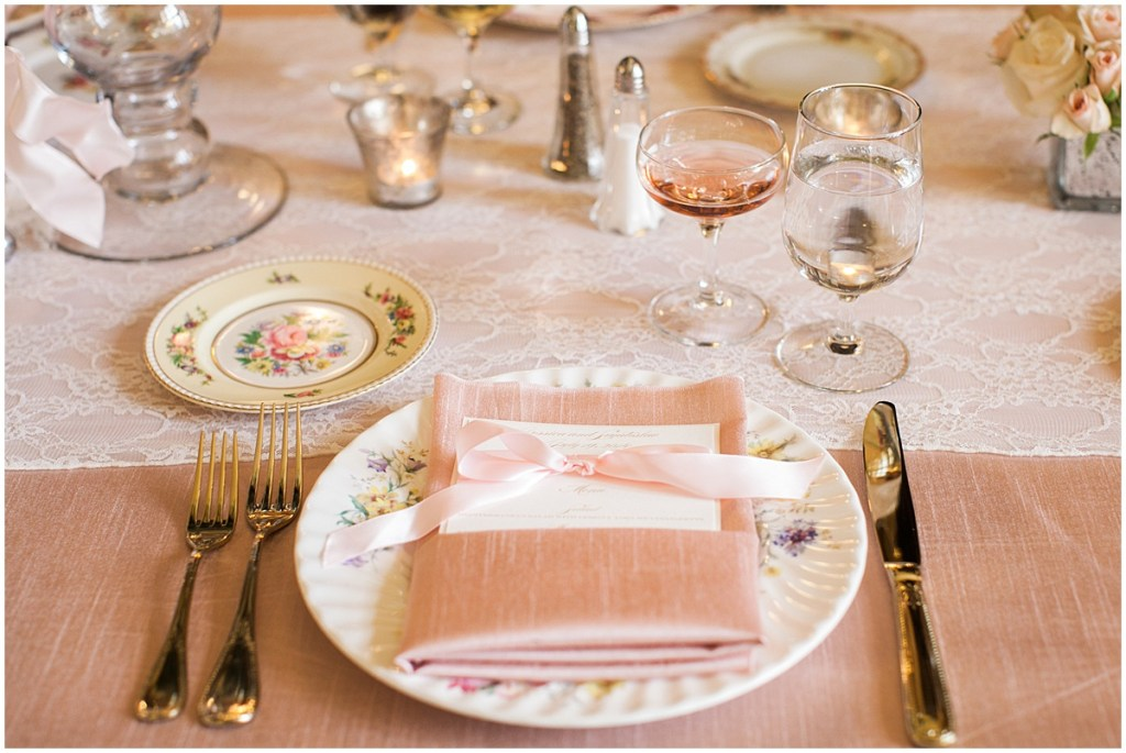 Wedding reception table place setting with vintage floral print china, gold cutlery, and a pink satin napkin sits on top of a pink satin tablecloth with an ivory lace table runner, Pacific Northwest wedding, Thornewood Castle wedding, wedding planning by Perfectly Posh Events, Photo by Stephanie Cristalli
