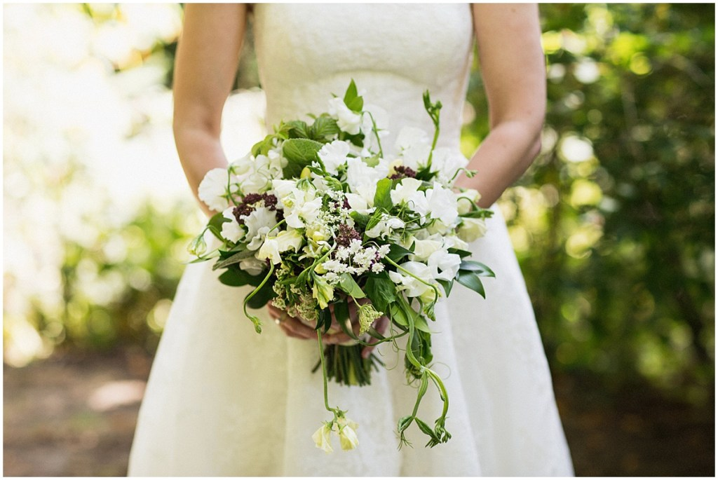 Close up of bride posing with her bridal bouquet made of ivory and burgundy flowers with touches of greenery, urban wedding, Within Sodo wedding, Seattle event planner, Perfectly Posh Events, Photo by Jenny J Photography