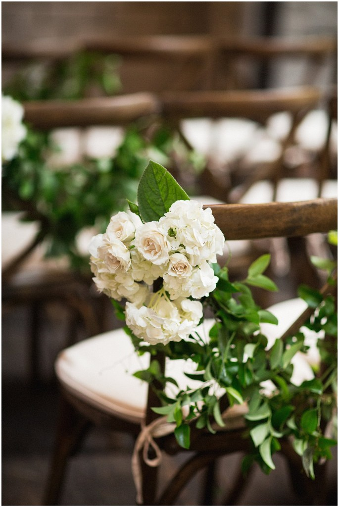 Close up of rustic wood chairs set up for a wedding ceremony decorated with ivory florals and plenty of greenery, urban wedding, Within Sodo wedding, Seattle event planner, Perfectly Posh Events, Photo by Jenny J Photography