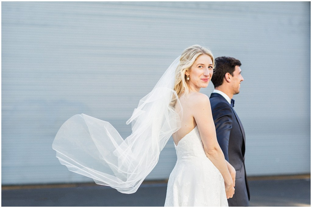 Bride and groom pose outside while the bride's sheer veil floats in the wind, urban wedding, Within Sodo wedding, Seattle event planner, Perfectly Posh Events, Photo by Jenny J Photography