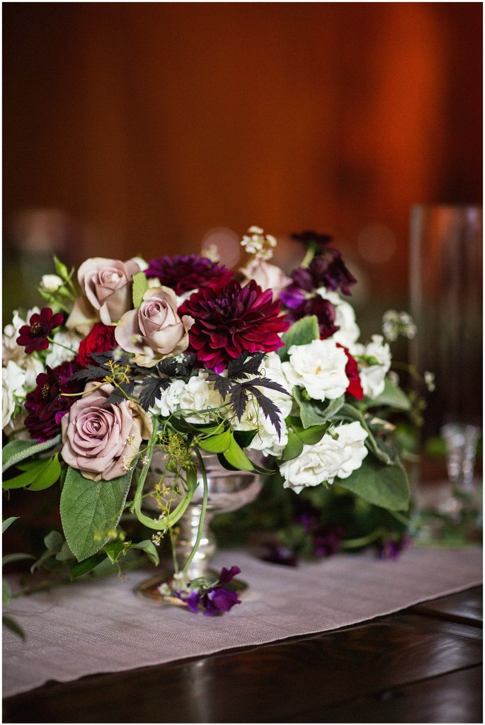 A wedding reception table centerpiece with blush, burgundy, and ivory florals with touches of greenery in a silver vase sits on a rustic wood table, urban wedding, Within Sodo wedding, Seattle event planner, Perfectly Posh Events, Photo by Jenny J Photography