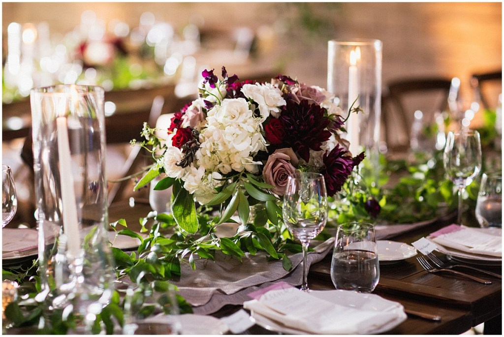 A dark and moody wedding reception table is set up with burgundy, blush, and ivory flowers and greenery along with candles in large hurricane holders, urban wedding, Within Sodo wedding, Seattle event planner, Perfectly Posh Events, Photo by Jenny J Photography