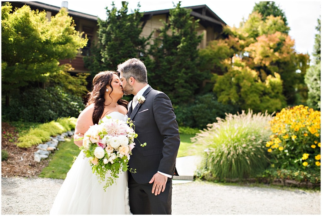 A bride and groom share a kiss outside in a garden, DeLille Cellars wedding, Woodinville winery, Washington wedding, Perfectly Posh Events wedding planning, Photo by Barbie Hull