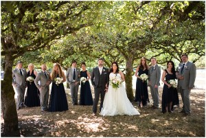 A bride and groom pose under trees in an orchard with their bridesmaids in navy colored gowns and groomsmen in charcoal grey suits, DeLille Cellars wedding, Woodinville winery, Washington wedding, Perfectly Posh Events wedding planning, Photo by Barbie Hull