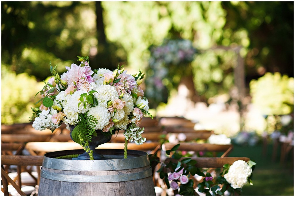 A large bouquet with ivory, pink, and peach colored flowers with pops of greenery in an iron urn sits on top of a wine barrel, DeLille Cellars wedding, Woodinville winery, Washington wedding, Perfectly Posh Events wedding planning, Photo by Barbie Hull