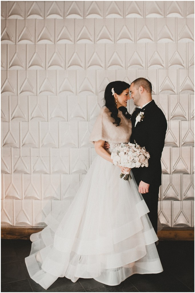 Bride in a ballgown wedding dress and faux fur shawl poses with her groom in front of a white textured wall, Edgewater Hotel, Seattle wedding, Washington wedding coordinator, Perfectly Posh Events, Photo by Carina Skrobecki