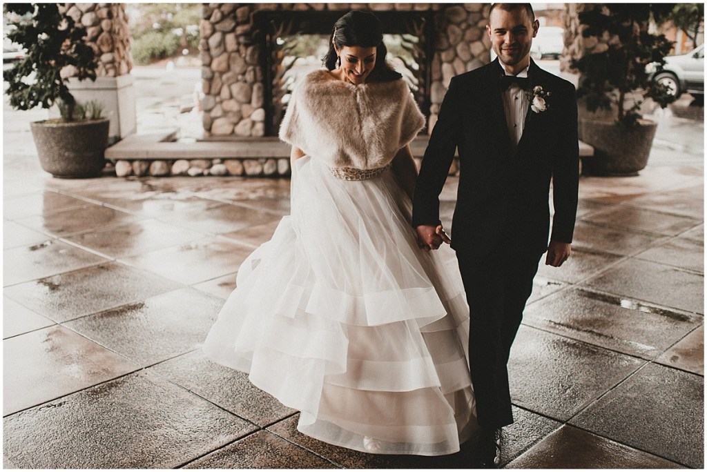 Bride in a ballgown wedding dress and faux fur shawl holds hands with her groom wearing a black tuxedo, Edgewater Hotel, Seattle wedding, Washington wedding coordinator, Perfectly Posh Events, Photo by Carina Skrobecki