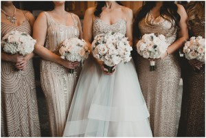 Close up of a bride posing with her bridesmaids wearing sequined gowns in varying shades of gold and champagne while holding white floral bouquets, Edgewater Hotel, Seattle wedding, Washington wedding coordinator, Perfectly Posh Events, Photo by Carina Skrobecki