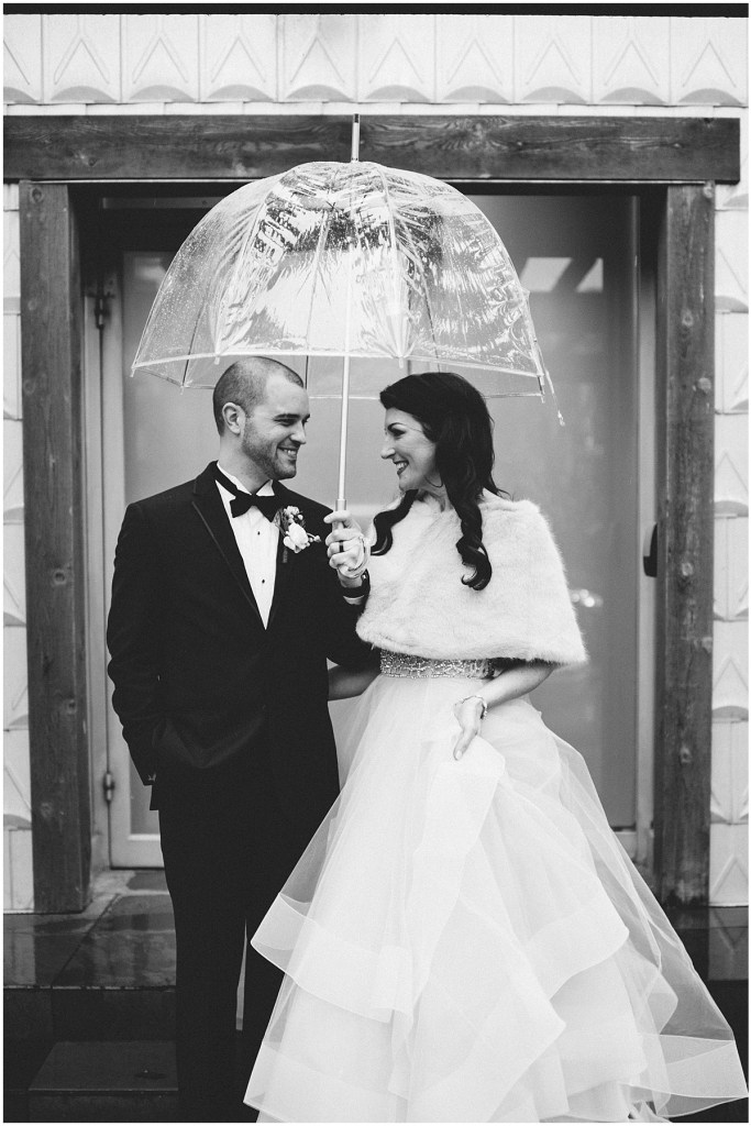 Black and white photo of a bride and groom smiling at each other under a clear umbrella as the rain falls on them, Edgewater Hotel, Seattle wedding, Washington wedding coordinator, Perfectly Posh Events, Photo by Carina Skrobecki