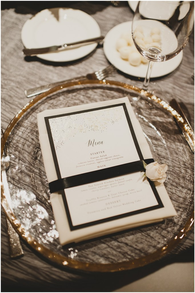 Wedding dinner place setting featuring a clear glass charger edged with gold and a custom designed menu wrapped in a black ribbon, Edgewater Hotel, Seattle wedding, Washington wedding coordinator, Perfectly Posh Events, Photo by Carina Skrobecki