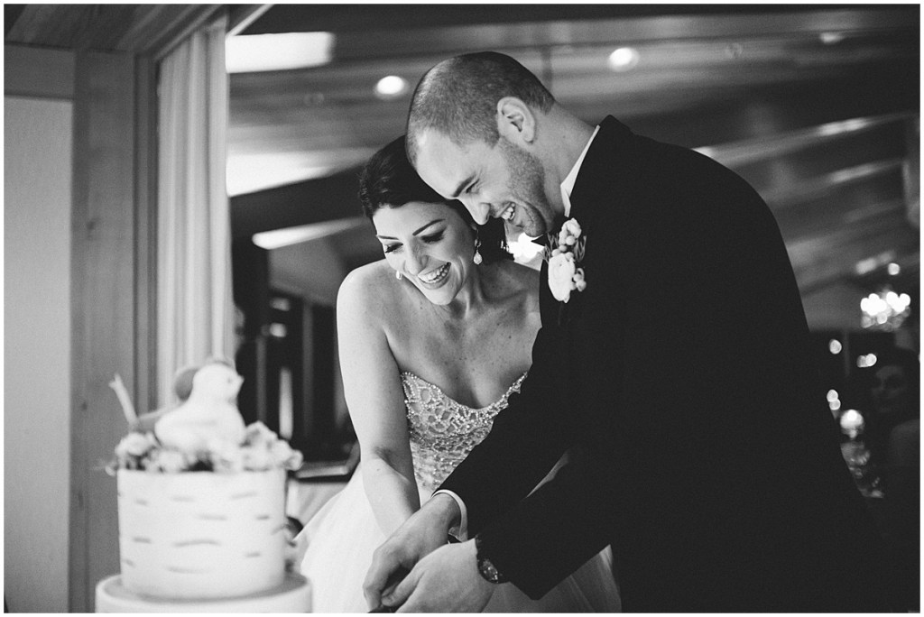 Black and white photo of bride and groom smiling as they cut into their wedding cake, Edgewater Hotel, Seattle wedding, Washington wedding coordinator, Perfectly Posh Events, Photo by Carina Skrobecki