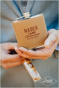 Closeup of a groomsmen in a grey suit holding a flask with a custom leather covering featuring the couple's wedding date, Fremont Foundry, Seattle wedding, Perfectly Posh Events wedding planning, Photo by Laurel McConnell Photography