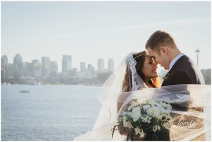 Bride and groom share an embrace while the bride's veil floats in the wind with downtown Seattle and the Space Needle in the background, Fremont Foundry, Seattle wedding, Perfectly Posh Events wedding planning, Photo by Laurel McConnell Photography