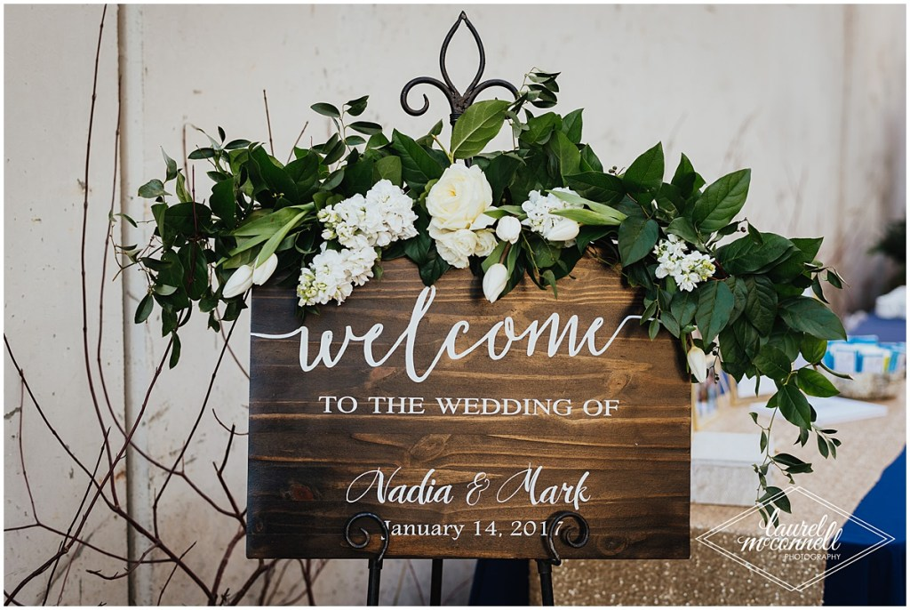Custom designed wedding welcome sign decorated with greenery and white flowers, Fremont Foundry, Seattle wedding, Perfectly Posh Events wedding planning, Photo by Laurel McConnell Photography