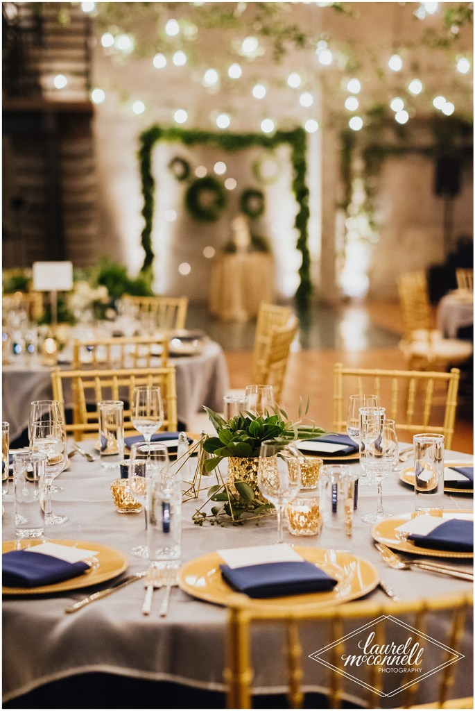Wedding dinner table covered in a light grey tabled cloth with a centerpiece with greenery in a small gold vase, gold geometric shapes, and votive candles and surrounded by gold chairs, Fremont Foundry, Seattle wedding, Perfectly Posh Events wedding planning, Photo by Laurel McConnell Photography