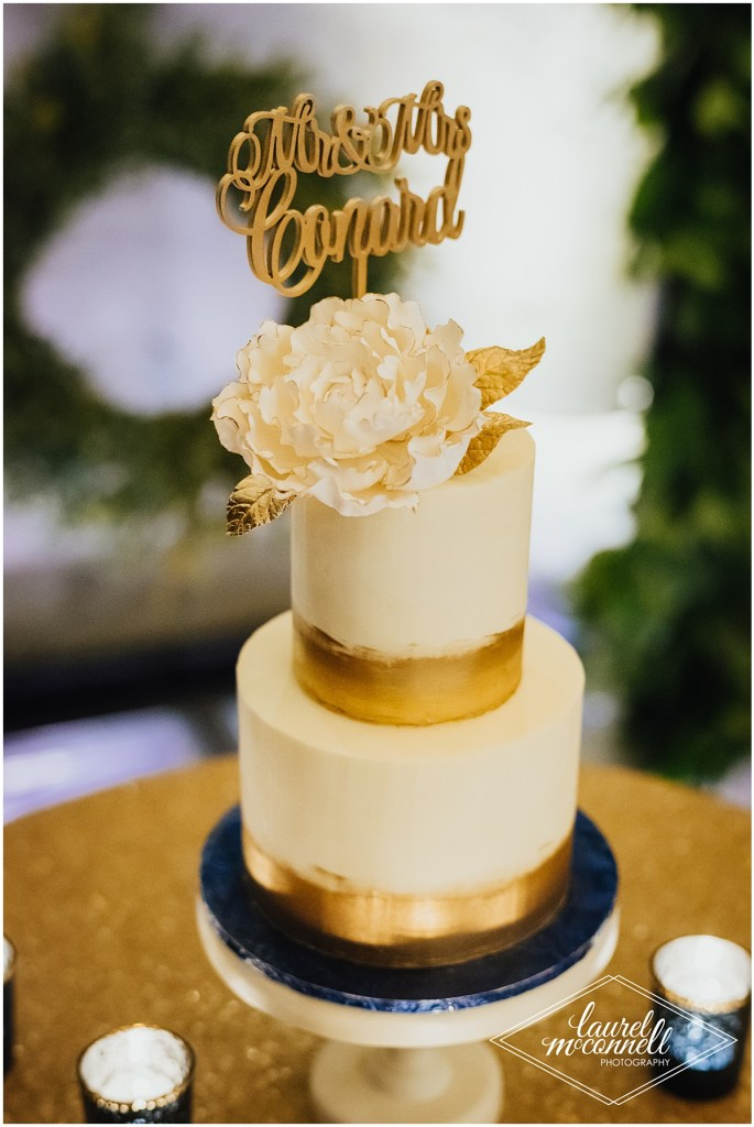Two tier wedding cake covered in white and gold metallic frosting and decorated with an edible white flower and a gold glitter sign with the couple