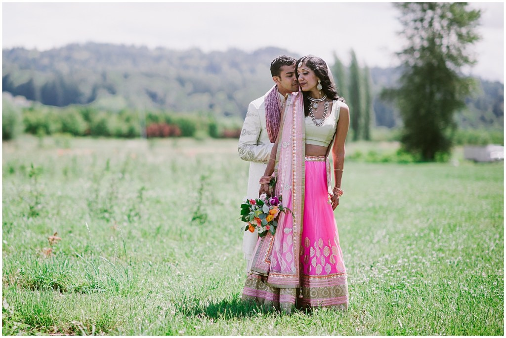 A bride and groom pose outside in a grass covered field, Dairyland wedding, Snohomish county wedding, Hindu wedding, wedding planning by Perfectly Posh Events, Photo by Barrie Anne Photography