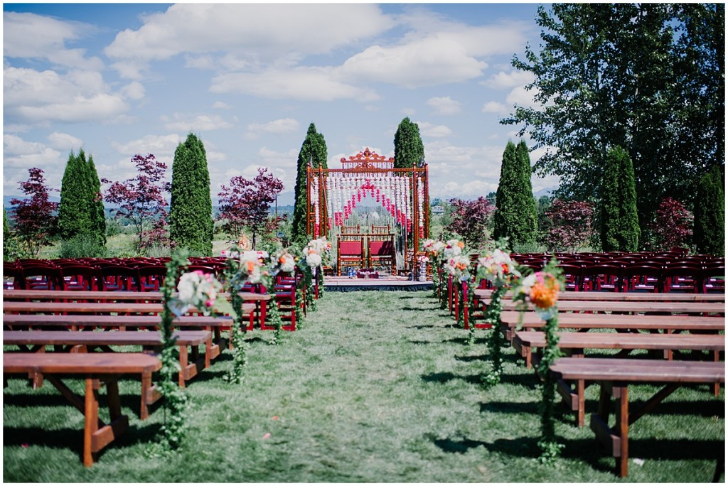 Outdoor wedding ceremony set up with rustic wood benches and a carved wood altar decorated with white and red flowers, Dairyland wedding, Snohomish county wedding, Hindu wedding, wedding planning by Perfectly Posh Events, Photo by Barrie Anne Photography