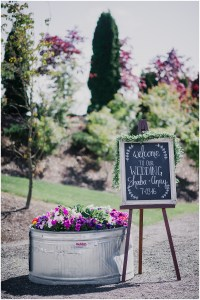 Wedding ceremony welcome sign hand drawn onto a chalkboard draped with greenery with a large tub of pink, purple, and white flowers sitting beside it, Dairyland wedding, Snohomish county wedding, Hindu wedding, wedding planning by Perfectly Posh Events, Photo by Barrie Anne Photography