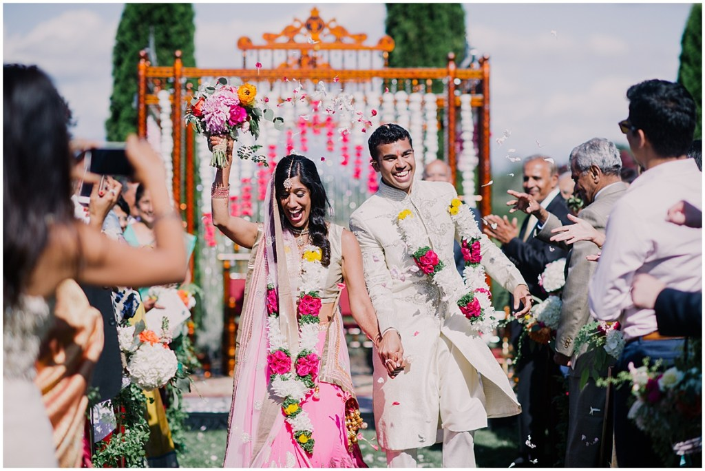Bride and groom celebrate as they walk back down the aisle after exchanging wedding vows as their guests shower them with flower petals, Dairyland wedding, Snohomish county wedding, Hindu wedding, wedding planning by Perfectly Posh Events, Photo by Barrie Anne Photography