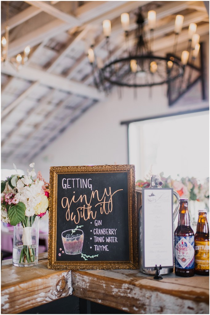 A rustic wedding reception bar with the couple's speciality cocktail menu hand drawn onto small chalkboard, Dairyland wedding, Snohomish county wedding, Hindu wedding, wedding planning by Perfectly Posh Events, Photo by Barrie Anne Photography