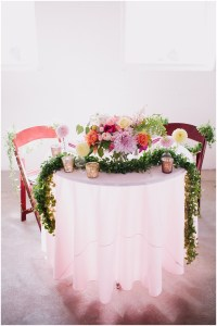 Bride and groom's wedding table set up with a centerpiece made of ivory, blush pink, and bright orange flowers surrounded with greenery and votice candles, Dairyland wedding, Snohomish county wedding, Hindu wedding, wedding planning by Perfectly Posh Events, Photo by Barrie Anne Photography