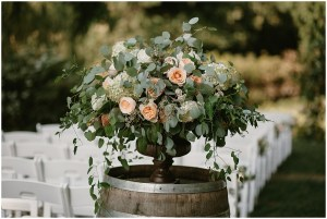 A large floral bouquet bursting with peach and ivory colored flowers and an abundance of greenery sits on top of a wood wine barrel, DeLille Cellars winery, Woodinville Washington wedding, event planning by Perfectly Posh Events , Photo by Kristen Marie Parker