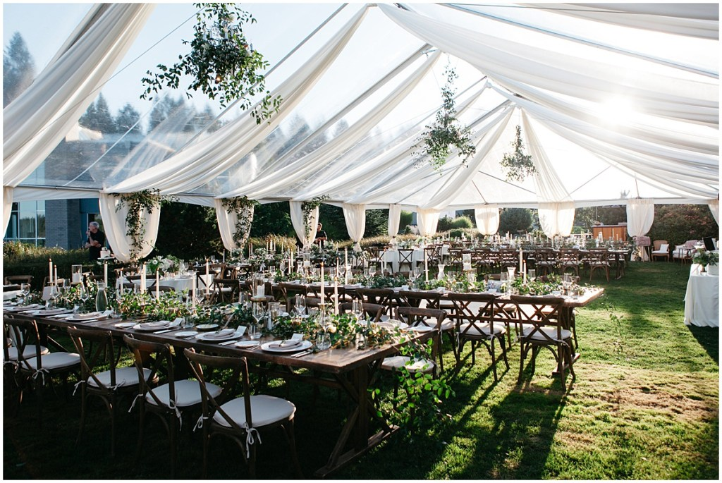 A beautiful outdoor wedding reception set up in a tent featuring dramatic chandeliers covered in greenery. PNW outdoor summer wedding by Washington wedding designer Perfectly Posh Events. Photo by Kate Price Photography.