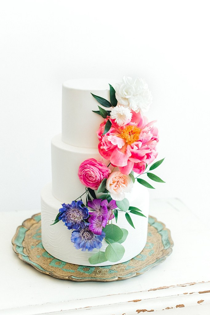 3-tier wedding cake with lush rainbow floral detail by Dream Cakes. Click for more cake inspiration and to learn more about Portland wedding cake bakery owners, Johanna and Megan of Dream Cakes, as they sit down for an interview by Portland wedding coordinator Perfectly Posh Events. Photo credit: Lauryn Kay Photography. #perfectlyposhevents