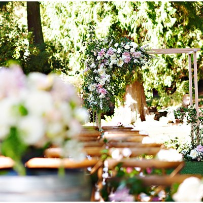 Garden ceremony with lush flowers and large ceremony arch with asymmetrical flowers and greenery   Whimsical and Romantic Wedding at DeLille Cellars   Wedding Planning & Design by Perfectly Posh Events   Wedding Photos by Barbie Hull Photography   Wedding Flowers by Floressence   #perfectlyposhevents