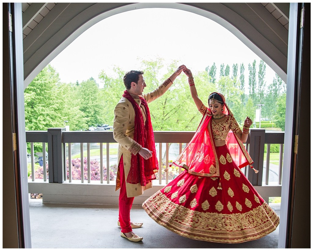 Hetal + Jake share a moment together before their wedding ceremony as Jake spins Hetal showing off her red and gold wedding sari.
