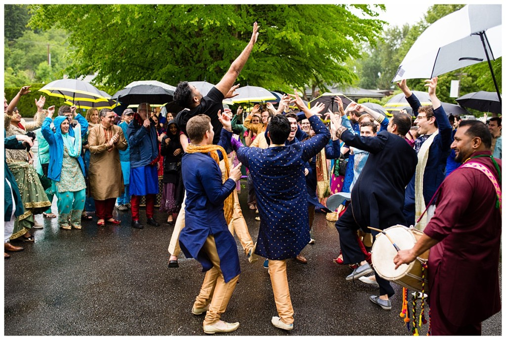 Guests donned in traditional and colorful Indian wear dance in the rain as part of Jake's baraat at Columbia Winery.