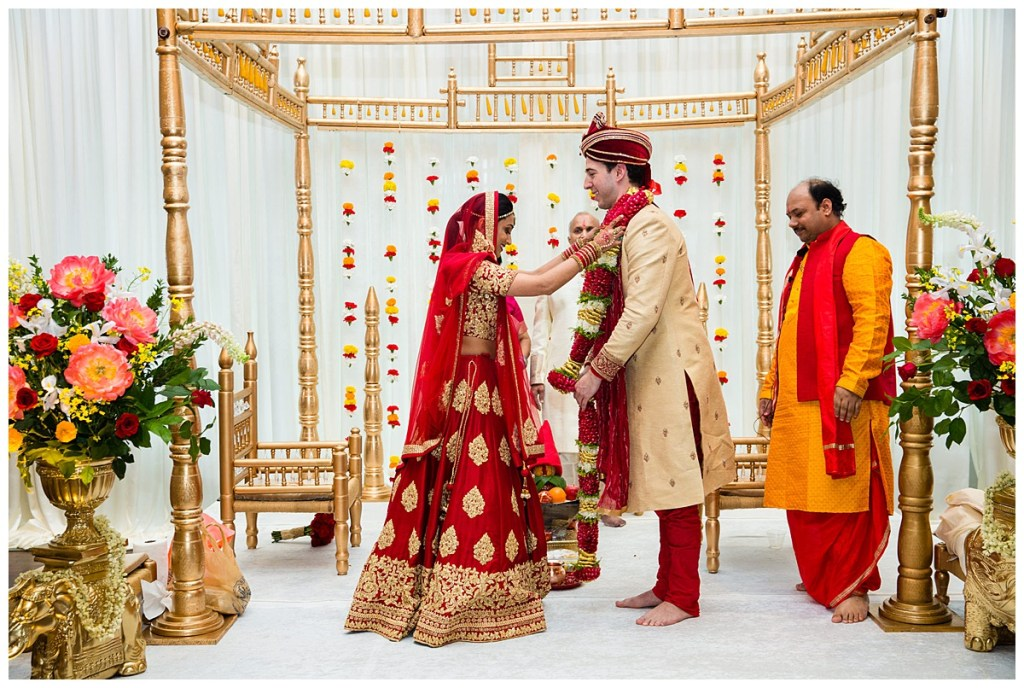 Hetal + Jake stand on top of the mandap that is decorated with bold and vibrant carnations for their traditional Indian wedding ceremony.