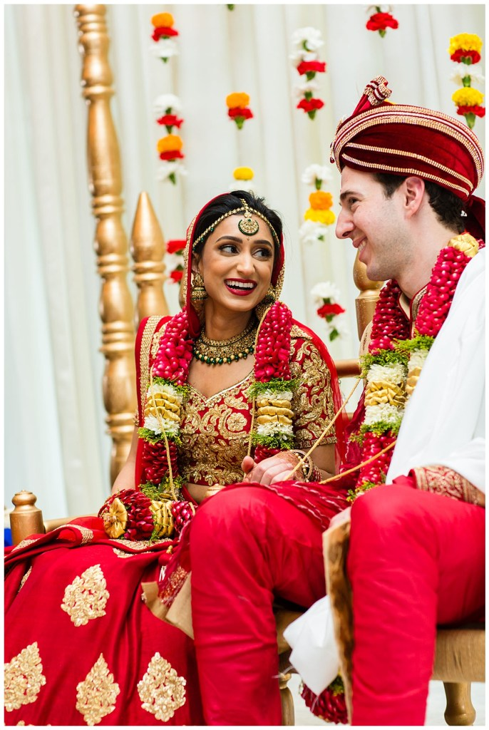 Hetal + Jake share a sweet moment as they are seated on top of the mandap that is decorated with bold and vibrant carnations for their traditional Indian wedding ceremony.