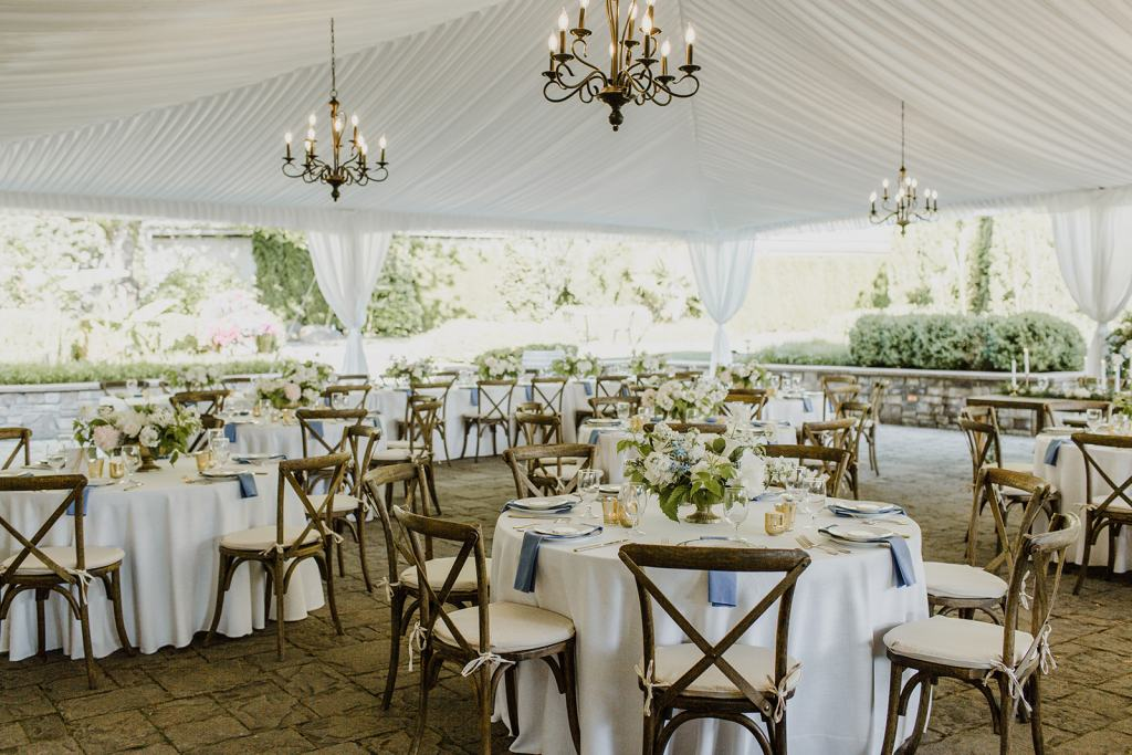 Pantone Color of the Year, Classic Blue, for 2020 is seen here in this waterfall napkin against a gold and white place setting on these wedding reception tables.