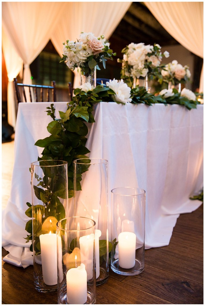 Hetal + Jake's florals featured a color palette of romantic blush, cream and white that decorated their head table along with candles.