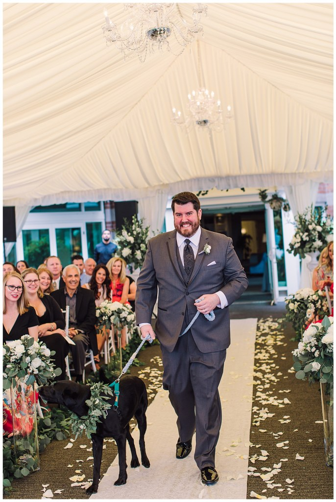 Elena + Travis wanted their dog, Aspen, to be a part of their special day. Here he is being walked down the Aisle by Elena's brother.