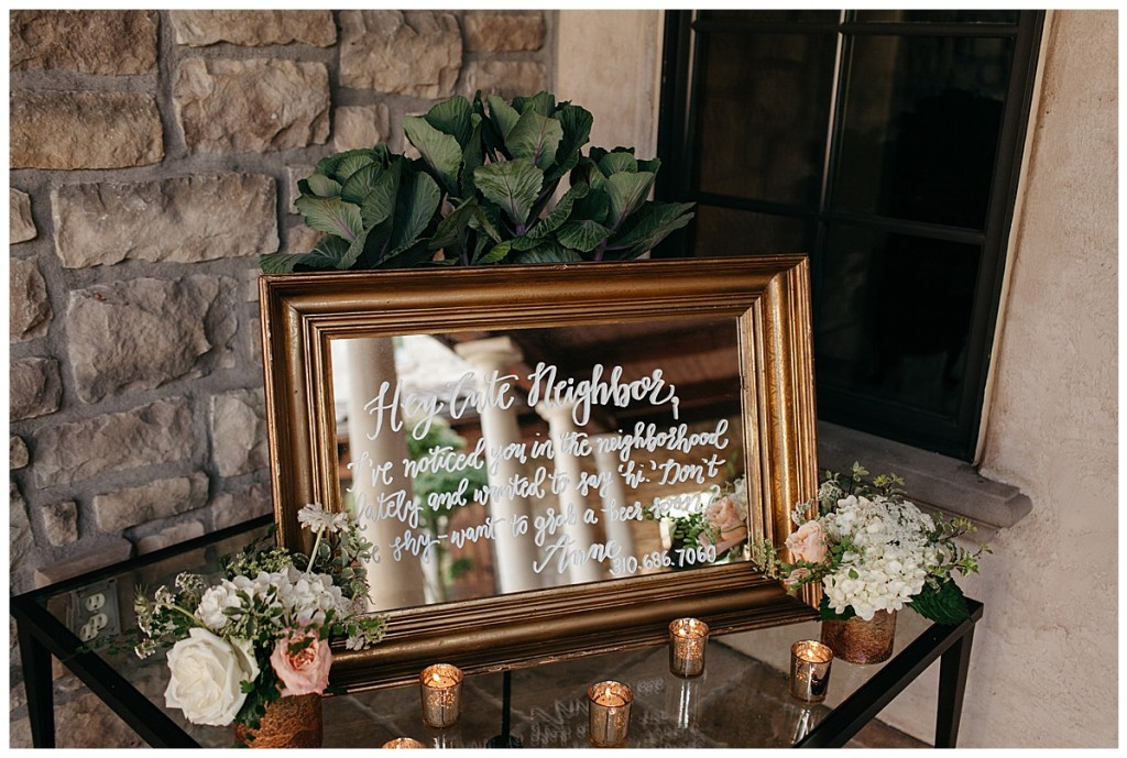 Gold mirror wedding sign with gold votive candles on welcome table.
