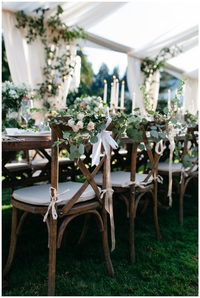 Wood wedding reception chairs with flowers and greenery tied to the back.