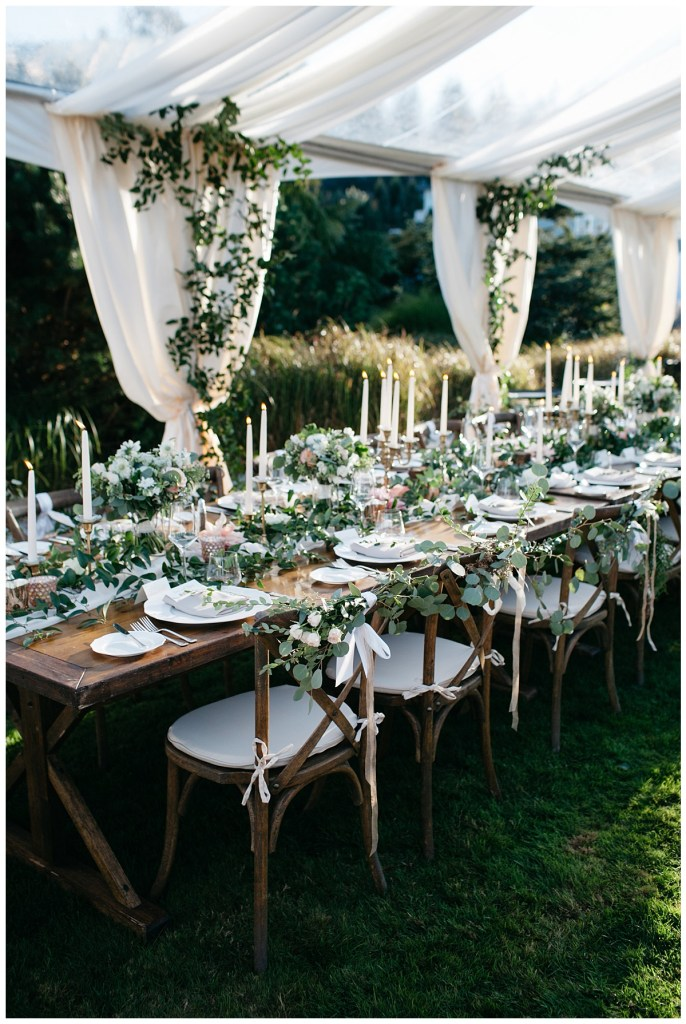 Wood wedding reception tables and chairs with greenery and white taper candles.