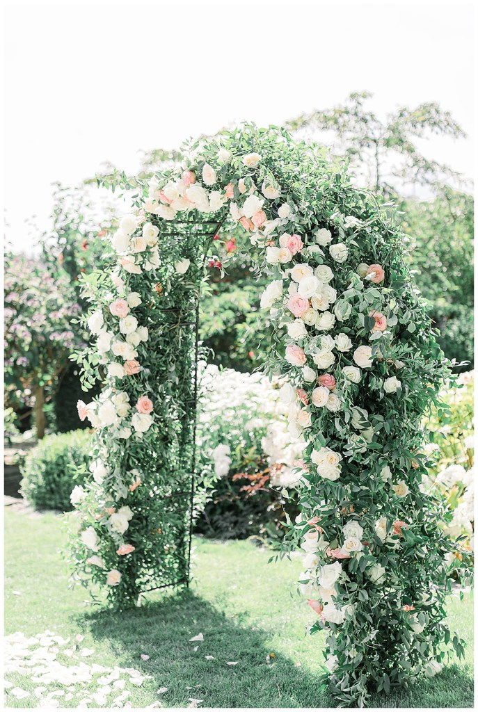 Floral arch with lush and full greenery and roses in white, cream and blush.