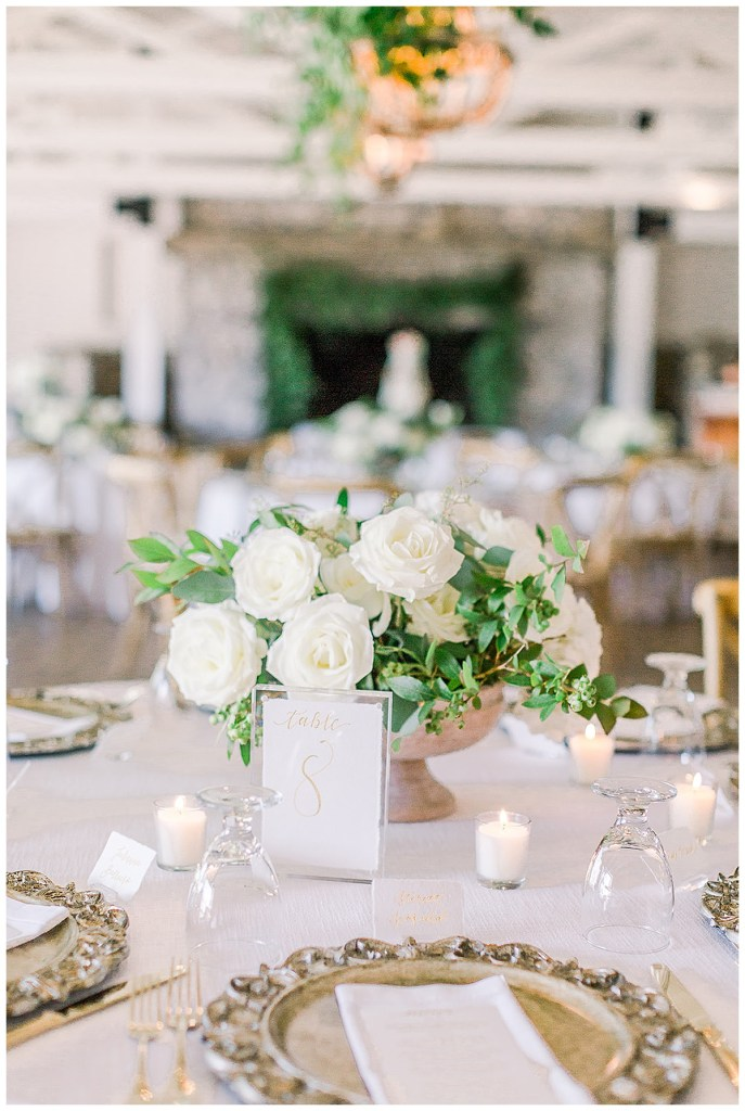Simple white rose and greenery wedding reception centerpiece with white and gold table numbers.